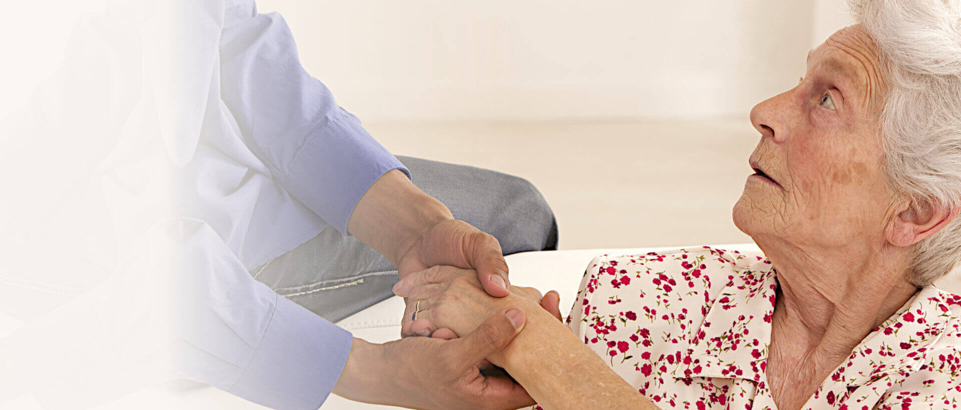 senior woman holding the hand of caregiver