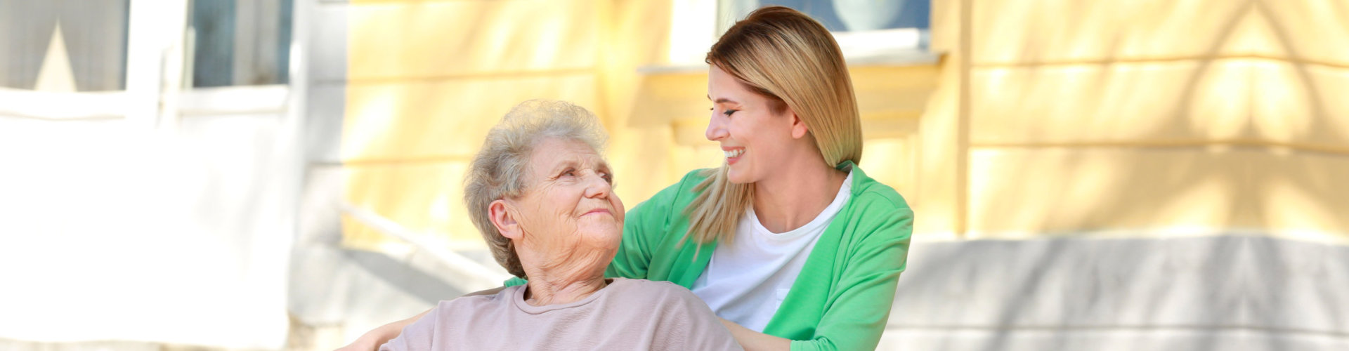 caregiver and senior woman looking at each other outdoor